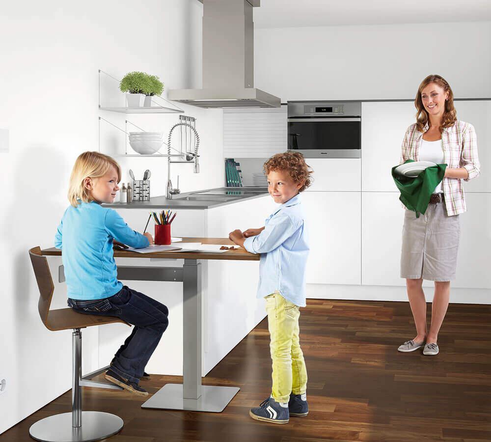 Kinder spielen am niedrigen Küchentisch